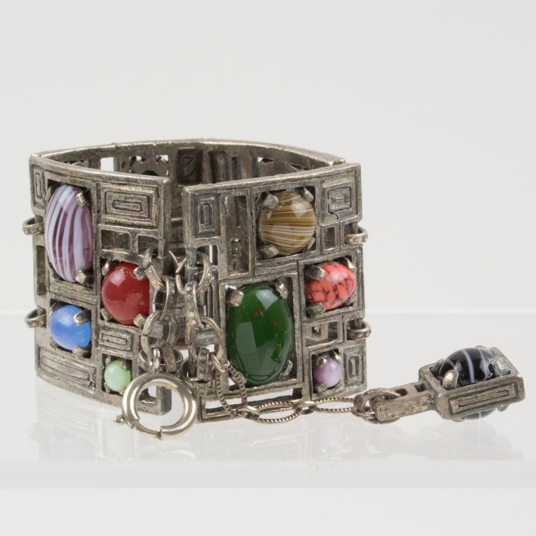 Interesting modernist metal and stones link bracelet. Geometric silvered metal elements, carved and see-thru, topped with assorted real gemstones, in assorted multicolor tones. Hook closing clasp with chain for length flexibility. Each element is
