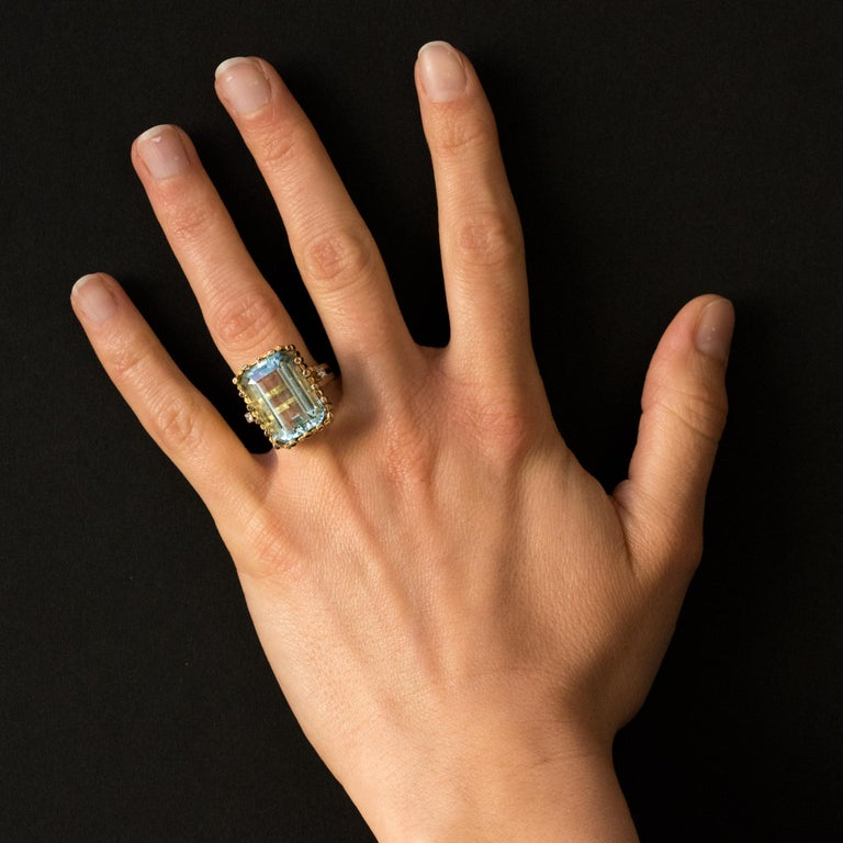 Ring in 14 Karats yellow gold, shell hallmark. Splendid modernist ring, it is set with an emerald- cut aquamarine shouldered on both sides on the departure of the ring by a brilliant- cut diamond. Weight of aquamarine: about 14.2 carats, total