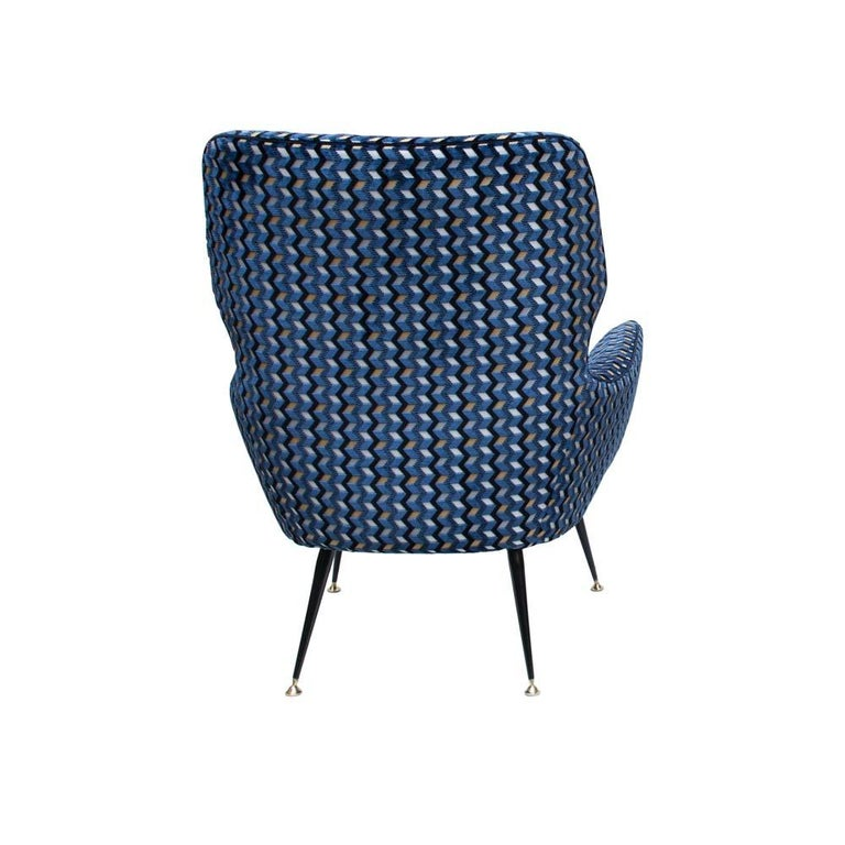 An of early 1950s Italian design armchair, completely upholstered wooden frame on black enamelled wrought iron tapered legs ending with brass feet. Newly upholstered in a precious geometric patterned precious velvet fabric in blue or gold or black