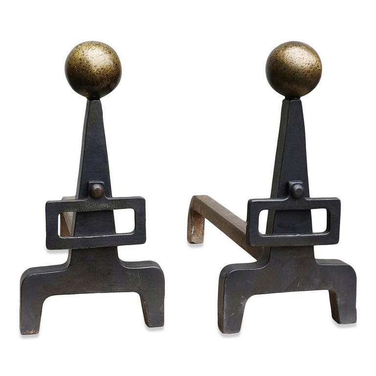 Modernist wrought iron andirons with buckle Hammered brass balls on top of each andiron.