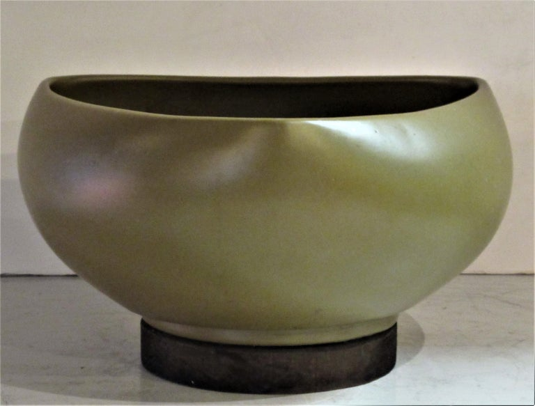 Rich pea color satin glazed architectural pottery planter with a symmetrical rounded spade shape form mounted on circular wood disc base by John Follis for Architectural Pottery, California, circa 1960.