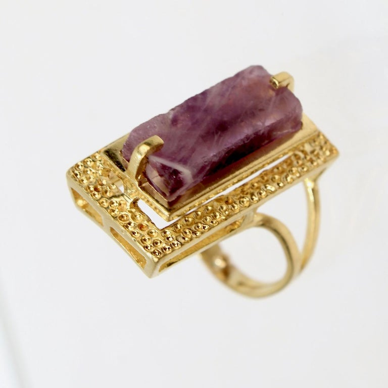 A very fine 18k gold and amethyst modernist cocktail ring.  With a rectangular cut amethyst gemstone prong set above a stippled and hammered platform setting that is supported by an asymmetrical split shank.  Very cool mid-century