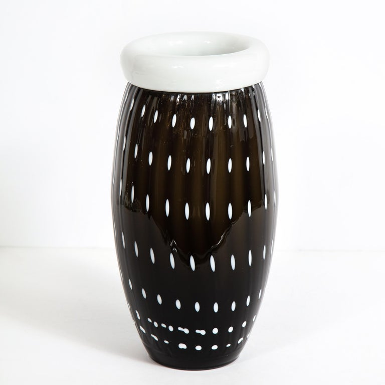 This elegant modernist black and white vase was realized in Murano, Italy- the island off the coast of Venice renowned for centuries for its superlative glass production. It features a cylindrical body that tapers to each end with a white banded