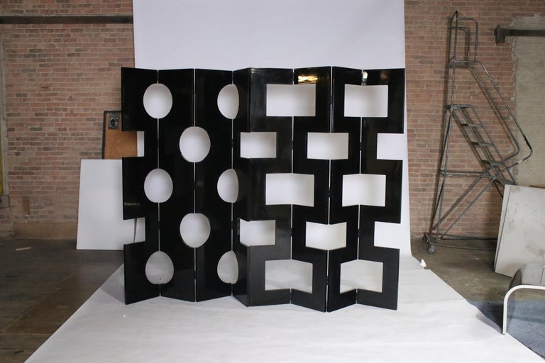 2 Four-panel modernist black lacquered room dividers sourced from vintage Saks 5th Avenue prop displays. Each panel is lacquered on both sides one with round circle holes and the other with square holes. They can be displayed together by hinges or