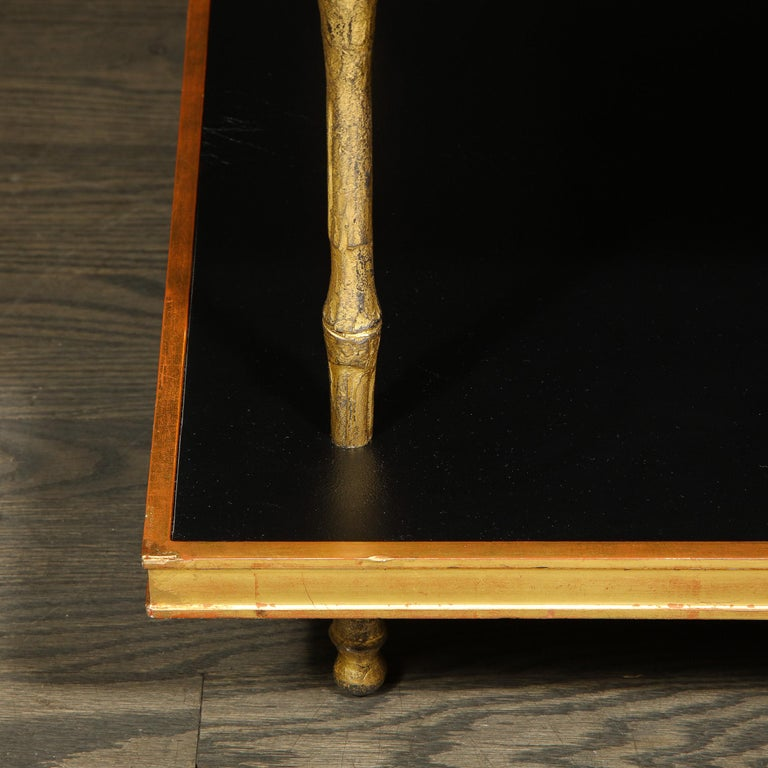 This elegant modernist two-tier cocktail table was realized in the United States by the esteemed atelier of Carole Gratale. The piece offers a rectangular body with a top and bottom tier circumscribed in giltwood with luxe black leather interiors.