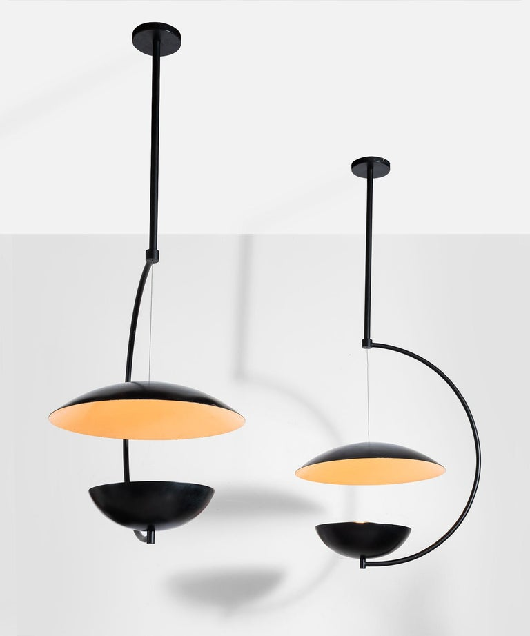 Crescent shaped modern pendant with hanging reflector disc.