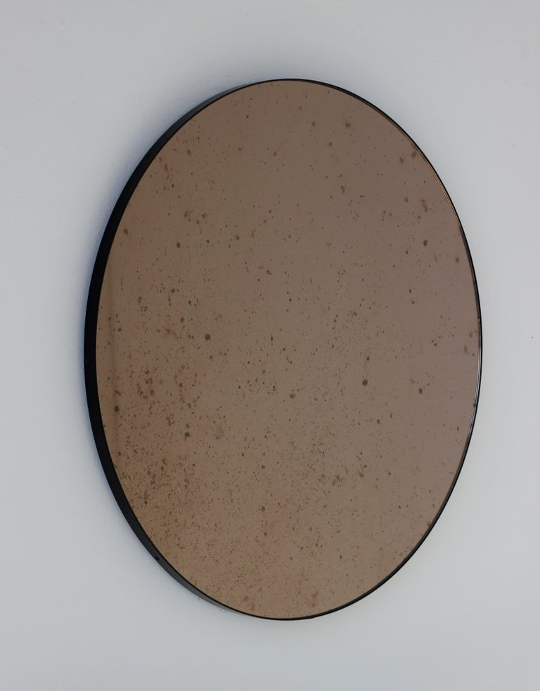 Delightful bronze tinted and antiqued round mirror with an elegant black frame. Designed and hand-crafted in London, UK.   Supplied fully fitted with a specialist hanging system for an easy installation.  Measures: Medium 60cm/23.6