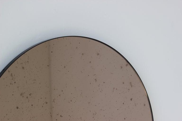 British Modernist Bronze Tinted Antiqued Orbis Round Mirror Black Frame, Customizable For Sale
