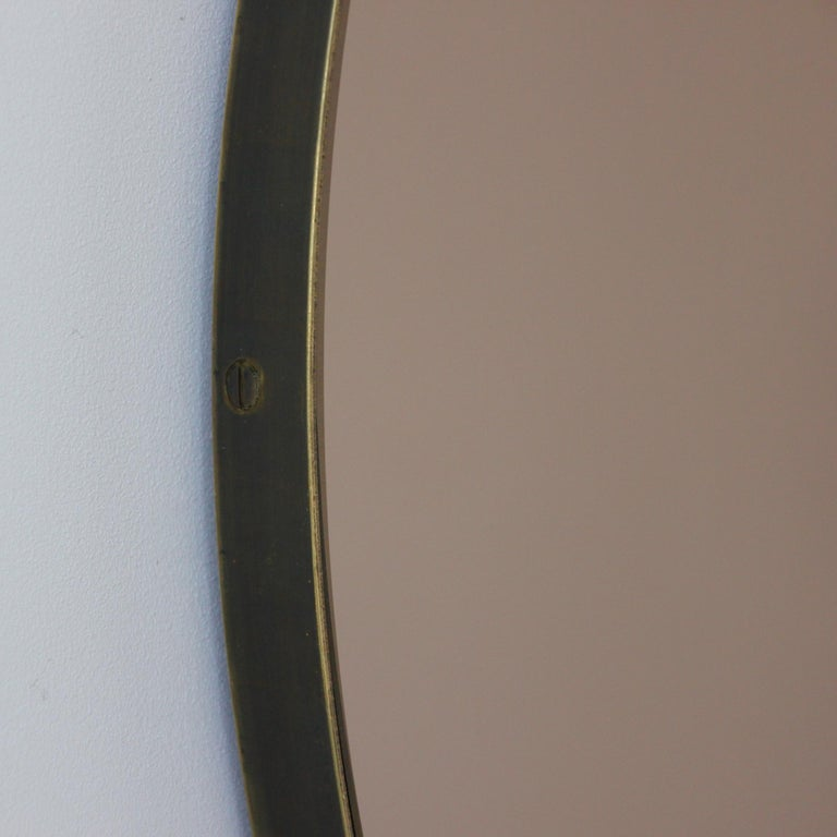 Smart bronze tinted round mirror with a bronze patina brass frame. Designed and handcrafted in London UK. The detailing and finish, including visible brass screws, emphasize the Craft and quality feel of the mirror, a true signature of our