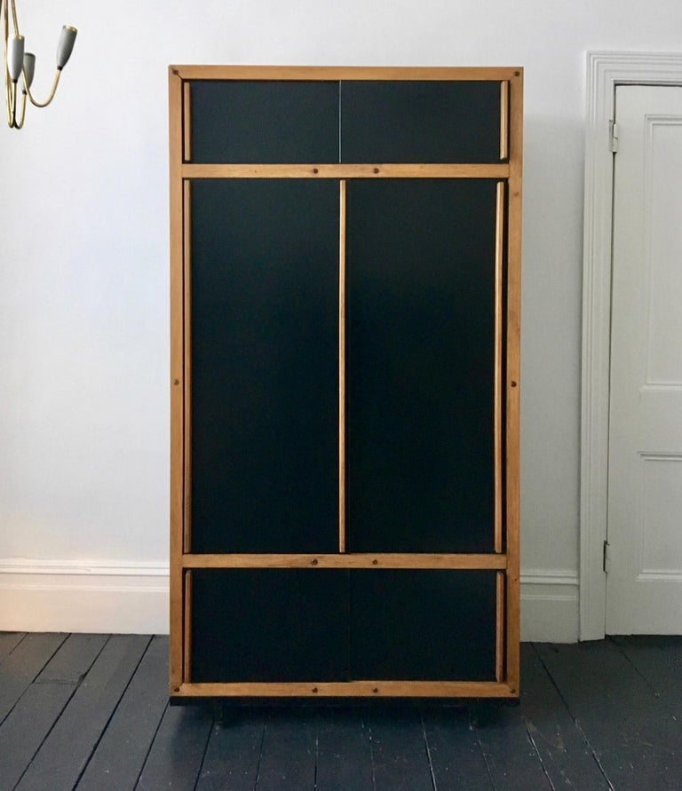 Modernist cabinet or armoire by André Sornay, mid-20th century, France. A simple design of clean lines, the main black panels being outlined by the natural wood of the frame and handles of the sliding doors.  The armoire is composed of wooden board