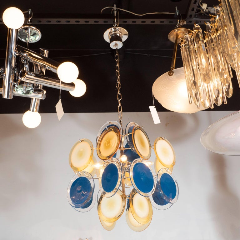 This sophisticated and vibrant chandelier was realized in Murano, Italy- the islands off the coast of Venice renowned for centuries for their superlative glass production. It features an abundance of handblown cerulean and straw yellow hued discs