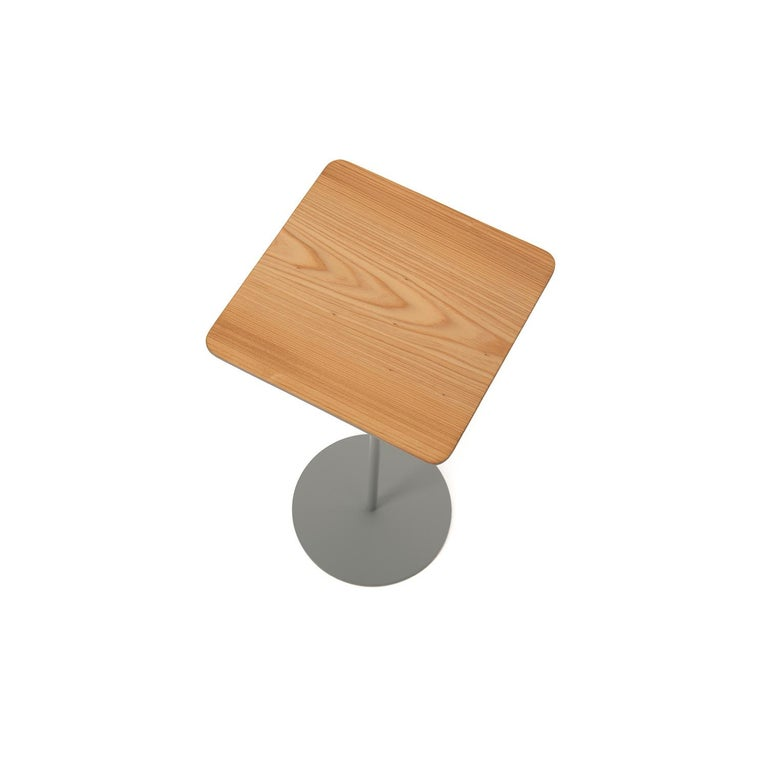 This square top cypress table sits upon a slender, gray stem with a circular base.