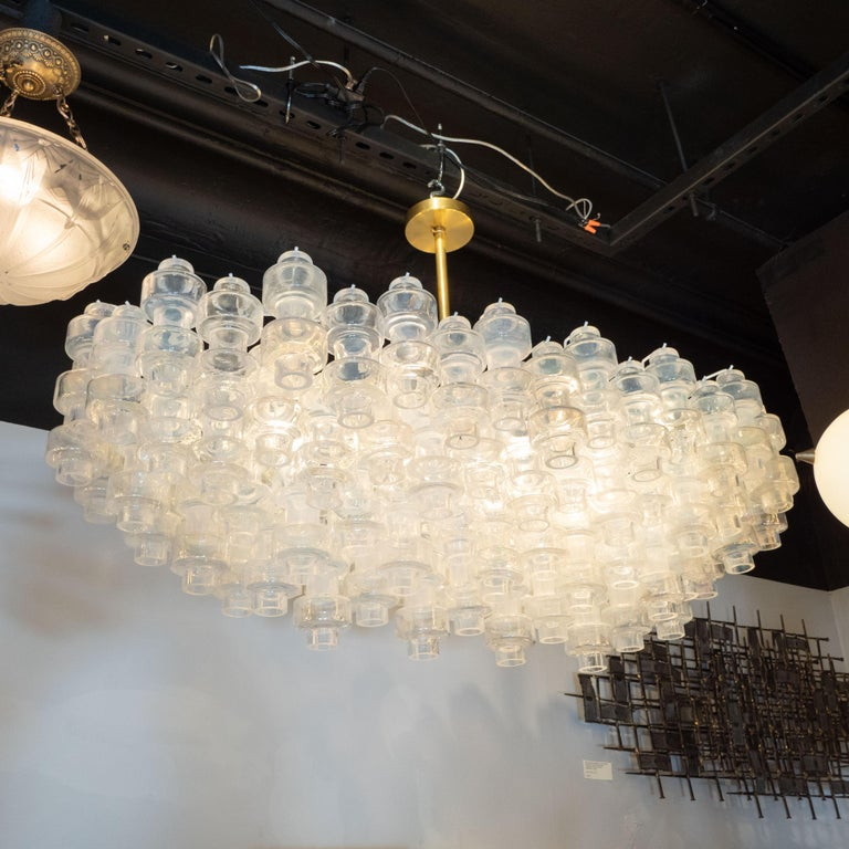 This stunning Murano glass chandelier was handblown in Murano, Italy the island off the coast of Venice renowned for centuries for its superlative glass production. It features an oblong body consisting of an abundance of barbell shaped Murano glass