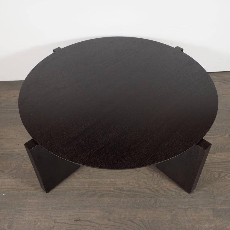 This sophisticated modernist cocktail table presents the simple elegance of contrasting geometric forms- a circular top and square legs- handcrafted in ebonized walnut. This table embodies the quiet refinement of American modern design. It is as