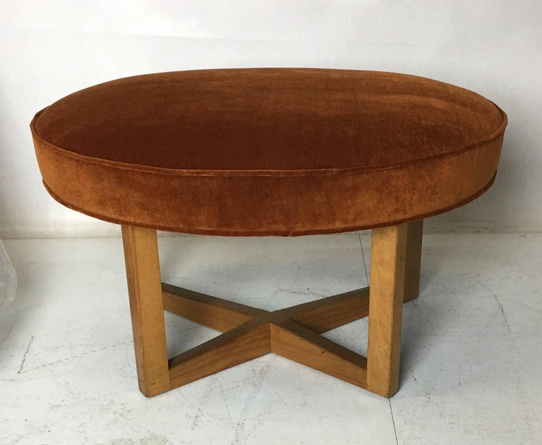 Amply scaled stool or ottoman with a free-form upholstered seat raised on a cruciform base by Paul Laszlo. The seat has been re-upholstered in luxurious heavyweight or backed JB Martin Cotton velvet. This fine piece makes for stylish occasional