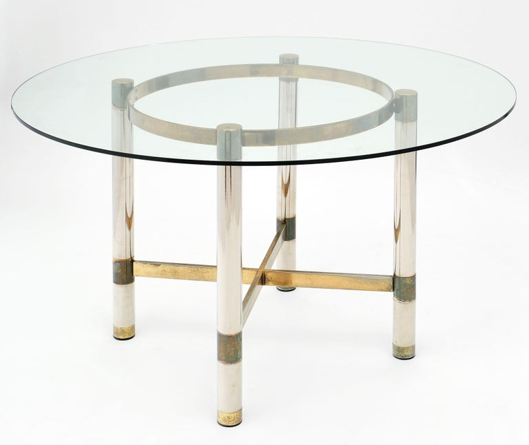 French modernist dining set. The table base is made of brass and chrome with a circular glass top. The chairs are upholstered with the original vinyl and feature Lucite on the backs of the chairs. We love the eye-catching details of this set. The