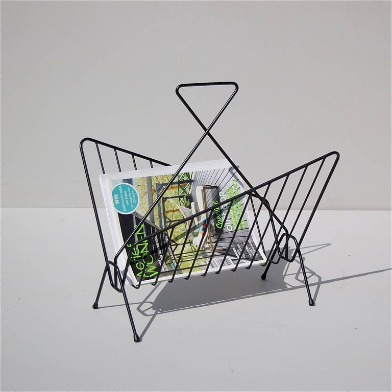 Mid-20th century geometric shaped magazine rack or newspaper holder in black lacquered metal. The trapezium shape of the side supports is identical, but in mirror image of each other. This creates a visually interesting and eye-catching effect. The