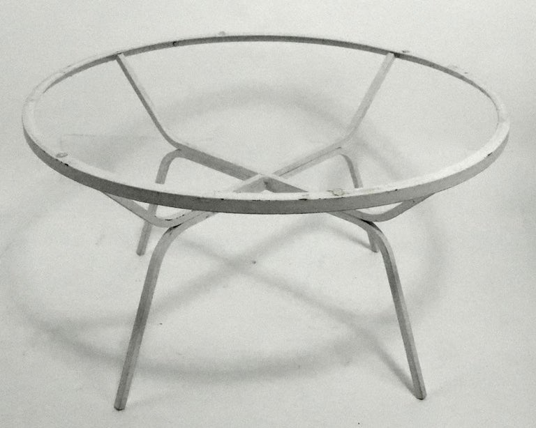 Unusual modern design occasional, side, cocktail, coffee table attributed to Salterini or possibly Woodard. The table has a circular plate glass top, and square stock wrought iron base. Currently in older white paint finish, which shows cosmetic