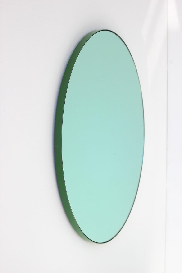 Green tinted round mirror with a green frame. Designed and handcrafted in London, UK.