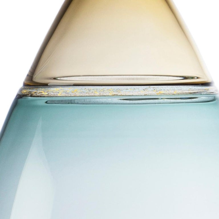 Voluminous, two-toned hand blown glass statement vessel features pale amber straw and blue-green tourmaline translucent hues. A speckled gold leaf seam emphasizes the shoulder. The Goccia (Italian:
