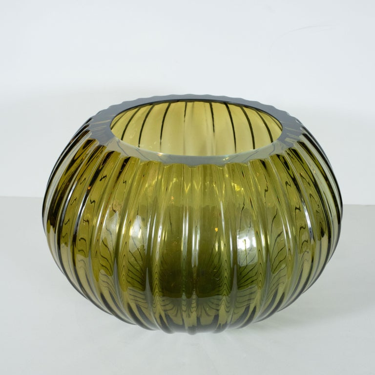 This stunning modernist decorative bowl was hand blown in Murano, Italy- the island off the coast of Venice renowned for centuries for its superlative glass production. It features a subtly ribbed body that expands to its equatorial centre before