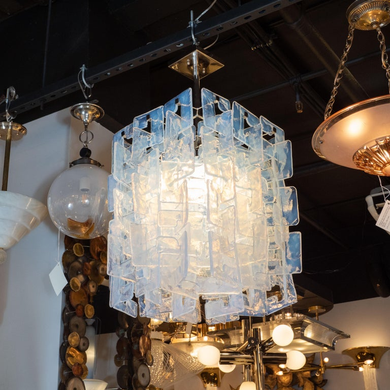 This stunning modernist chandelier was realized in Murano, Italy, the island off the coast of Venice renowned for centuries for its superlative glass production. It features rectangular bodies consisting of an abundance of translucent interlocking