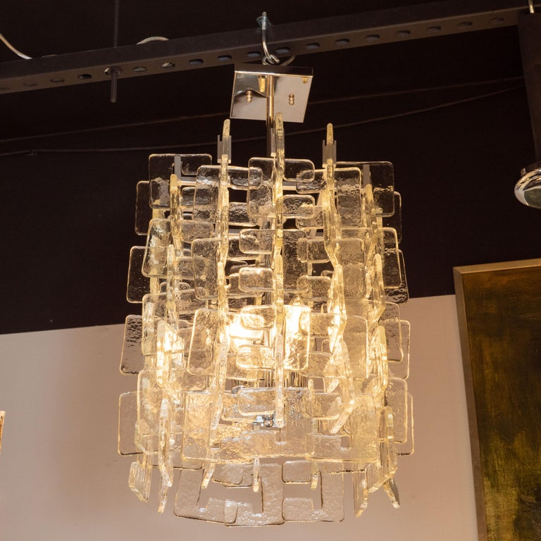 This gorgeous modernist chandelier was realized in Murano, Italy- the island off the coast of Venice renowned for centuries for its superlative glass production. It features an abundance of translucent c-shaped shades that elegantly interlock