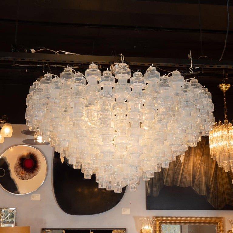 This outstanding Murano glass chandelier in the manner of Carl Fagerlund features an interlocking design consisting of numerous barbell shaped Murano glass shades hanging in a honeycomb formation. The glass is high quality Murano glass with an
