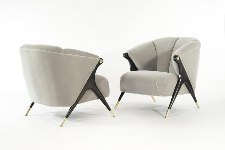Stunning and rare pair of lounge chair by Karpen of California, circa 1950s.  Newly upholstered in grey alpaca velvet, sculptural maple legs newly restored to their original ebonized finish, newly polished brass sabots and arm hardware.  Priced