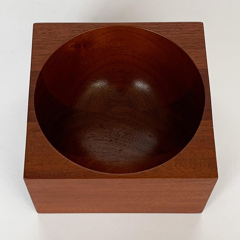 Modernist turned solid mahogany wood bowl by John Sage. Inspired by Poul Kjaerholm's marble PK-Bowl. Square form with concave half circle bowl. Inscribed: Bear Woodworking, John A. Sage, 1982. The original label states mahogany desk bowl.
