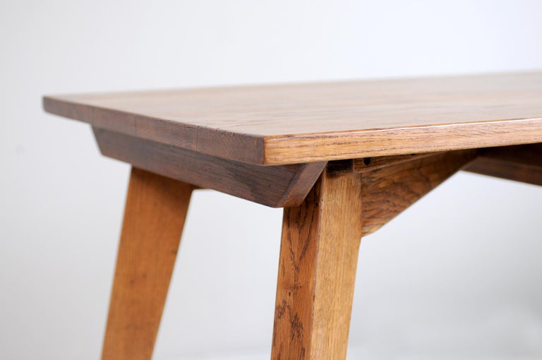Table in solid oak, France 1950. The top, reinforced by four cross-sections, has a central drawer sliding freely on both sides. The design of the base in the form of a compass, the use of blond oak, its gathered and dynamic line give this work of