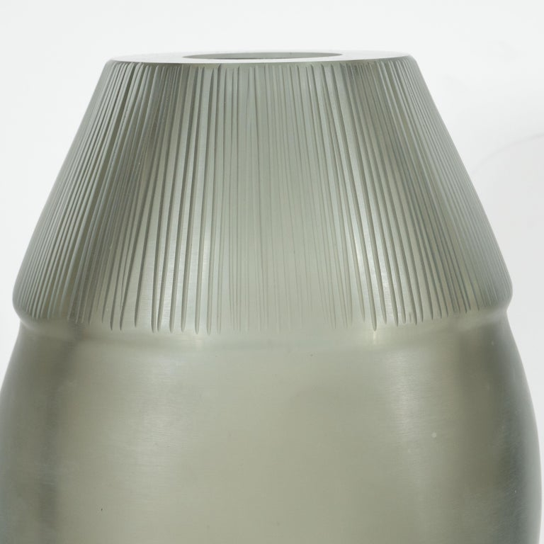 This stunning modernist vase was realized in Murano, Italy the island off the coast of Venice, renowned for centuries for its superlative glass quality. It features an ovoid form- resembling a stylized bullet- with ribbed shoulders that ascends into