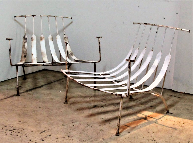 A spectacular pair of wrought iron lounge chairs with bull horn shaped backs / raised arms and low slung flat spring steel seats. These will take sling straps on armrests that will attach to outer top horn backs and loose cushion on seat frame.