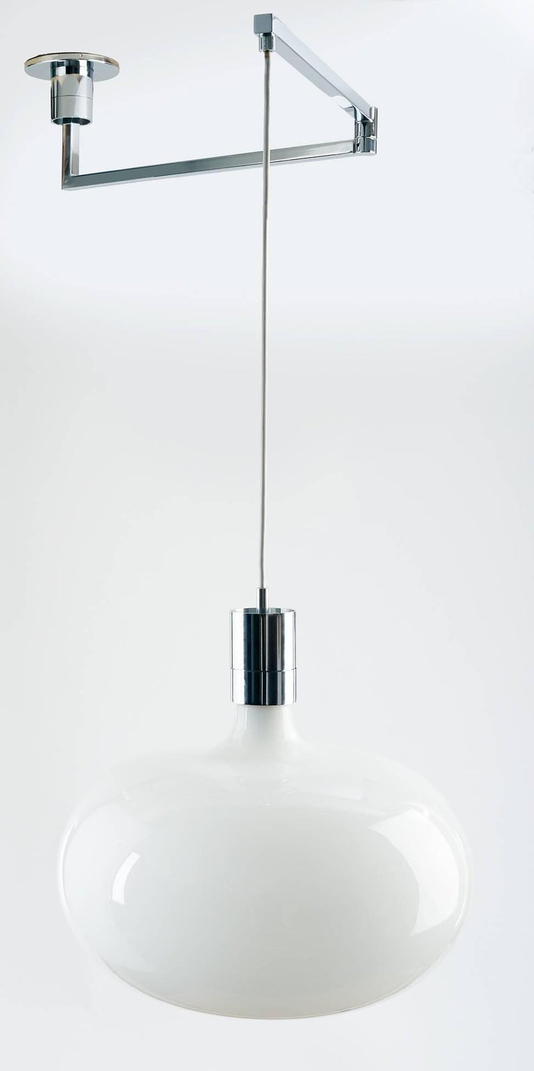Franco Albini (1905–1977)  Minimalist, early model adjustable-height pendant by Franco Albini, with a movable chrome-plated swing-arm and a sleek, dimpled opaline glass shade. Height is adjustable; maximum height is 45 inches.