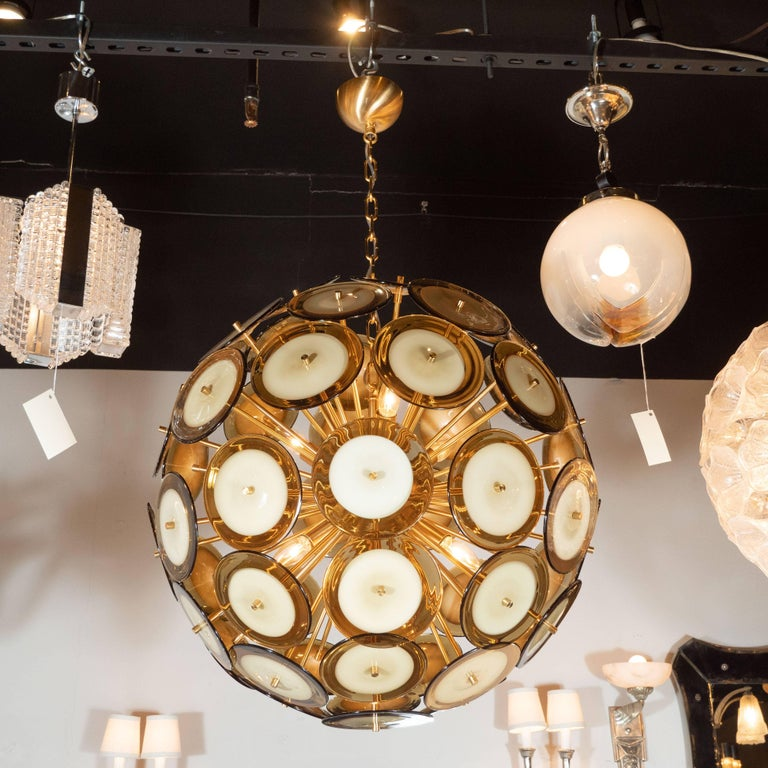 This sophisticated and stunning chandelier was realized in Murano, Italy- the islands off the coast of Venice renowned for centuries for their superlative glass production. It features an abundance of polished brass rods emanating from a central orb