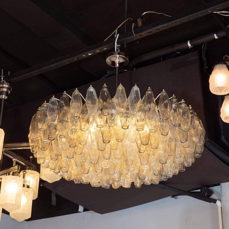 This stunning chandelier was realized by hand in Murano, Italy- the islands off the coast of Venice renowned for centuries for their superlative glass production. It features multiple tiers of polyhedral shades in alternating translucent hues of