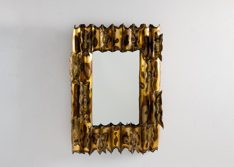 This remarkable mirror has a frame made up of an intriguing pattern of bisected brass cylinders, oxidized variously to create a beautiful almost natural effect that sets up order in contrast to disorder, creation to disintegration.
