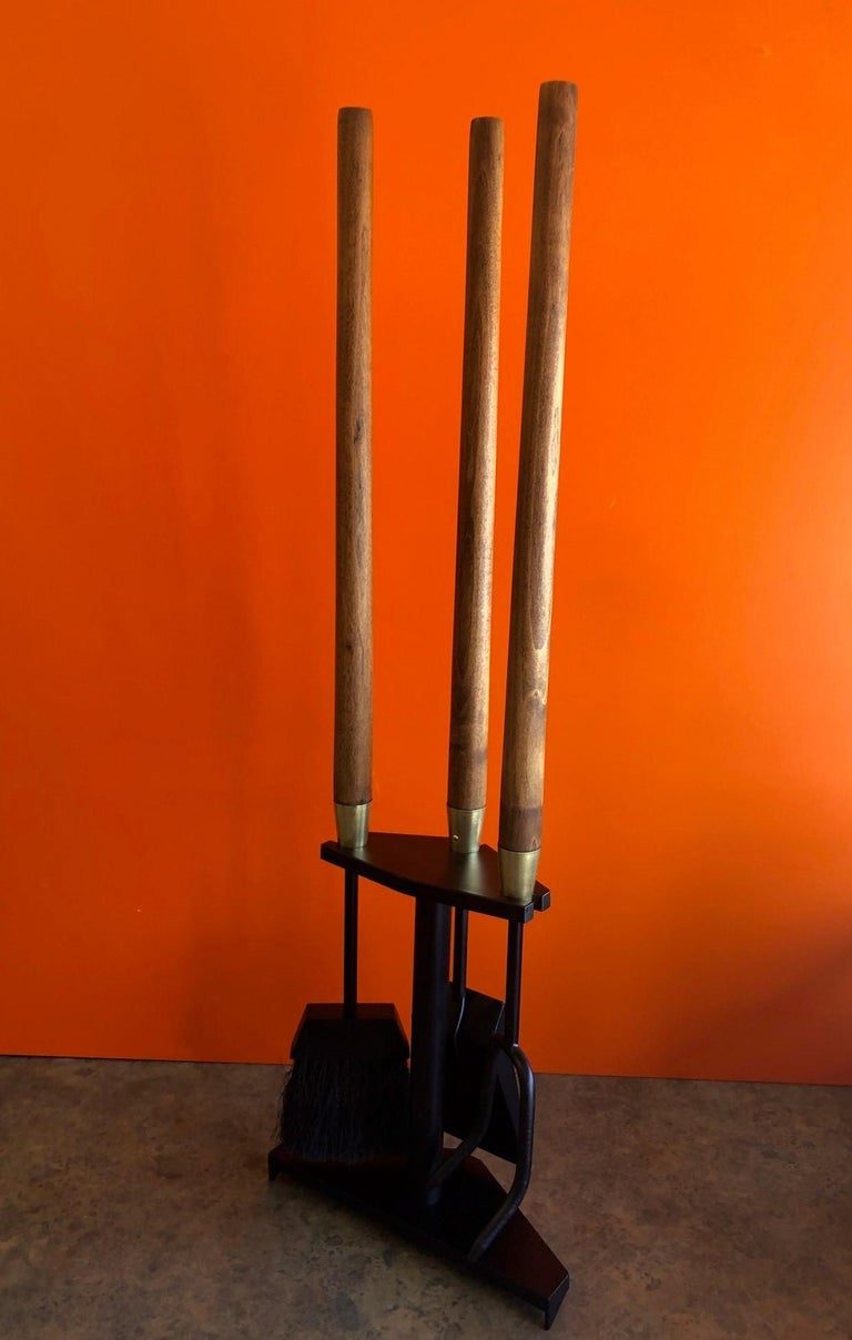 Modernist set of fire place tools in cast iron with brass fittings and walnut handles by Seymour Mfg. of Indiana, circa 1960s. There are three tools (shovel, brush and poker) and a triangular stand in excellent refinished condition. The set measures