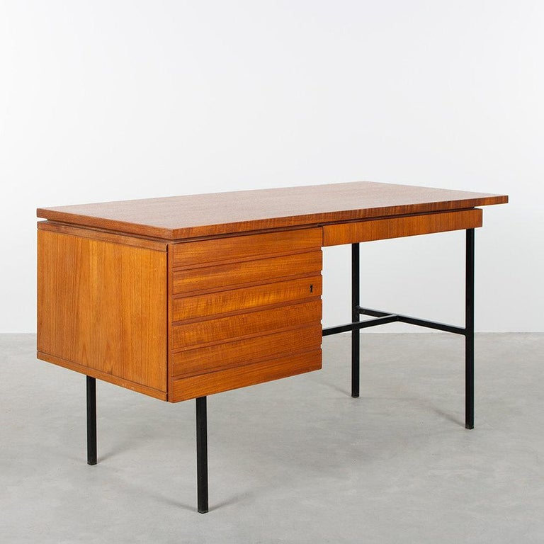 Elegant modernist small desk by an unknown designer. Teak veneer and black coated steel frame all in good vintage condition with minor traces of use.