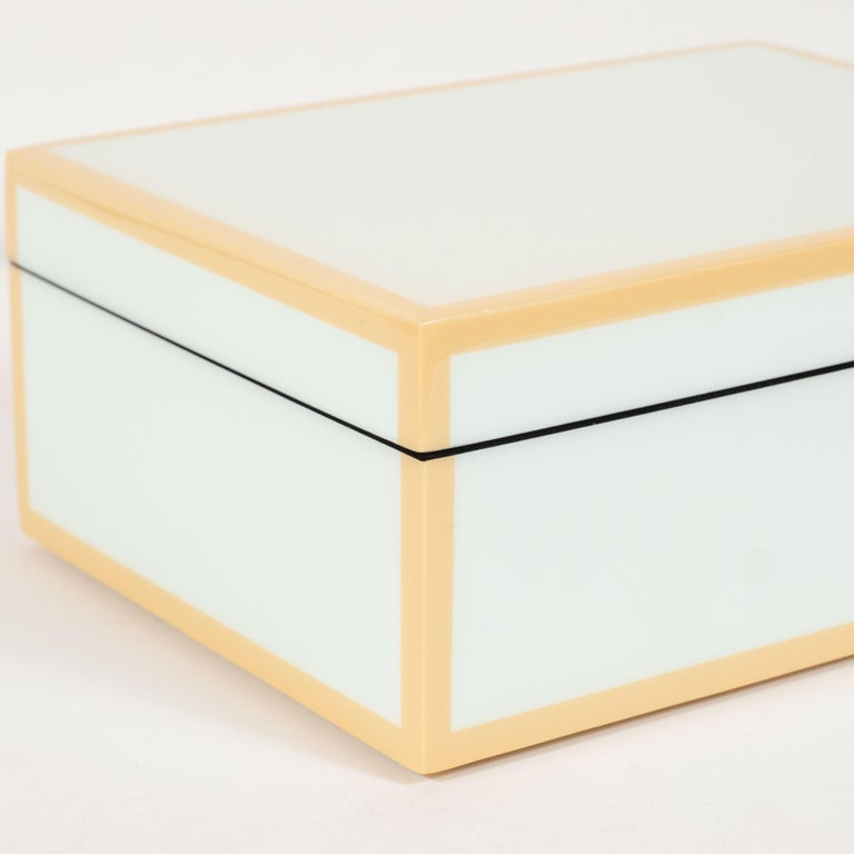 This elegant modernist lacquered box offers a square form with a lacquered exterior in a pale celadon hue with tan accents circumscribing each of the exterior edges. The interior of the box has been finished in black felt, testifying to the fact