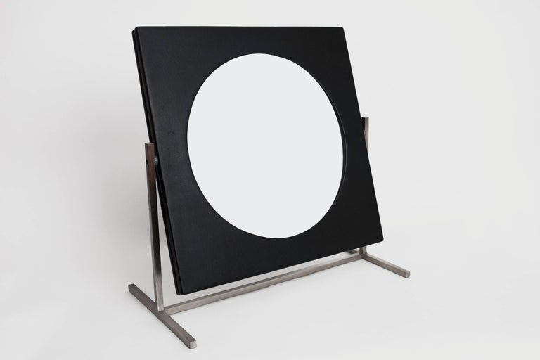 France, 1960's  A sleek, graphic modernist table or vanity mirror with rotating hinge, in brushed steel and black leatherette.  H 10.5 in. x W 19.5 in. x D 11 in.