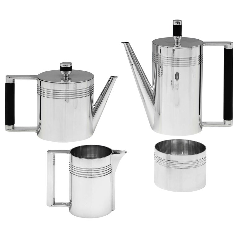 Hallmarked in Birmingham in 1995 by A. E. Jones, this handsome, Modernist design, sterling silver tea set, is batchelor sized, and features angular handles and reed detailing throughout. The teapot measures 4.25