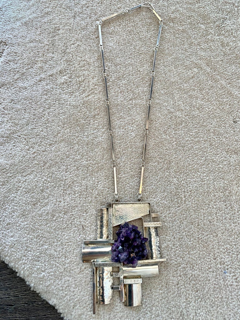 Artisan crafted sterling silver necklace in a modernist/ cubist design with raw amethyst crystal geode, marked sterling and signed by artist to backside of pendant (difficult to determine the signature). One of a kind cubic Brutalist design,