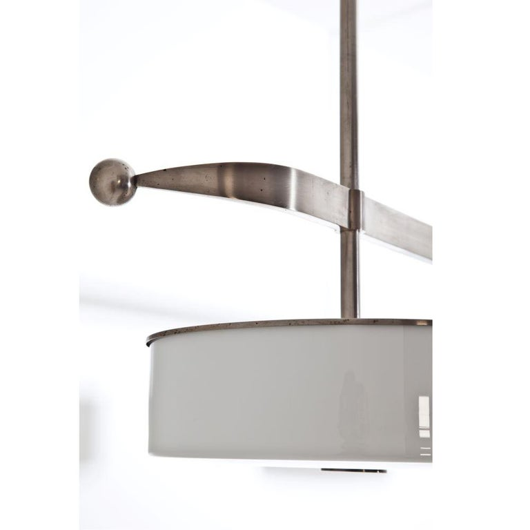Modernist nickeled brass ceiling light. Three light fixture with glass diffusers and  Incredible patina. Six sockets in total.