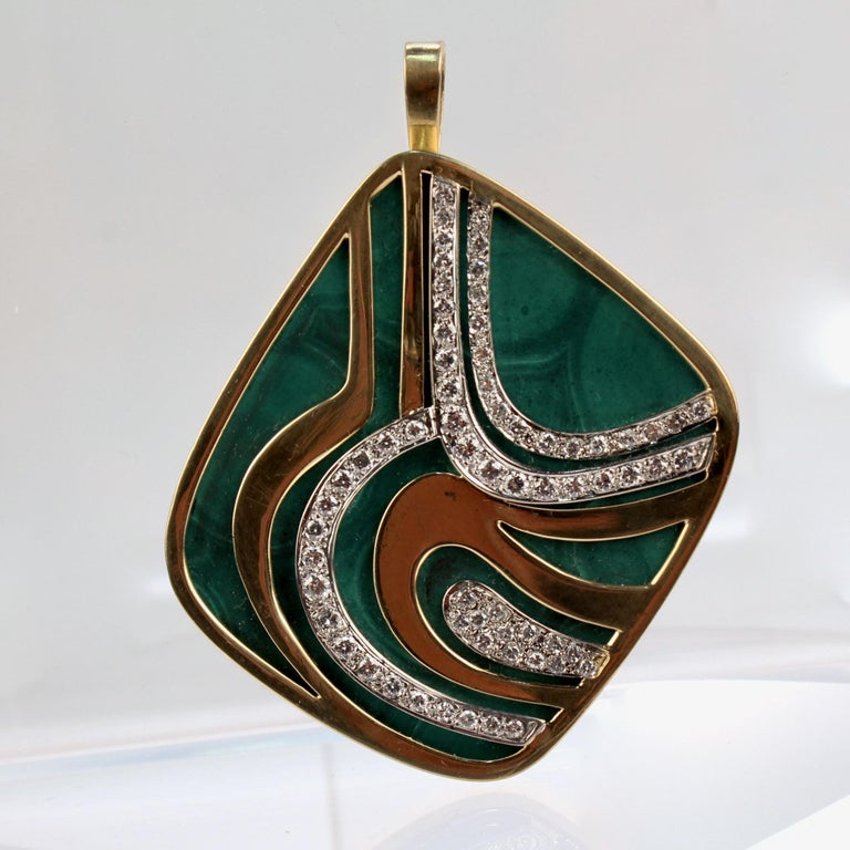 A very fine Swiss modernist 18k gold, diamond, and malachite pendant brooch by Weber & Cie.  With a large flat malachite cabochon bezel set in 18k gold.    Encased by an organic pattern of three bands of yellow gold and three bands of white gold