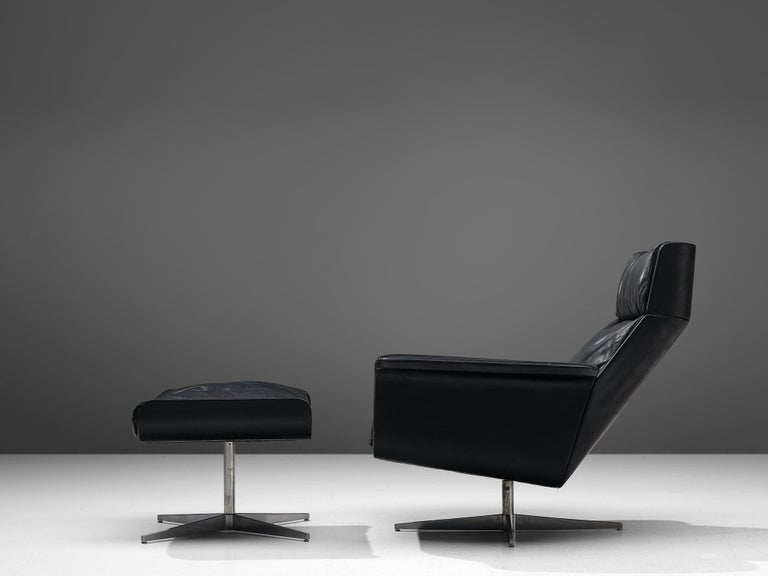 Lounge chair with ottoman, leather and metal, Germany, 1960s.  This German modern lounge chair with ottoman features a comfortable, tufted seat. The chair is build up in three parts or shells, creating a angled design from the side. Both the