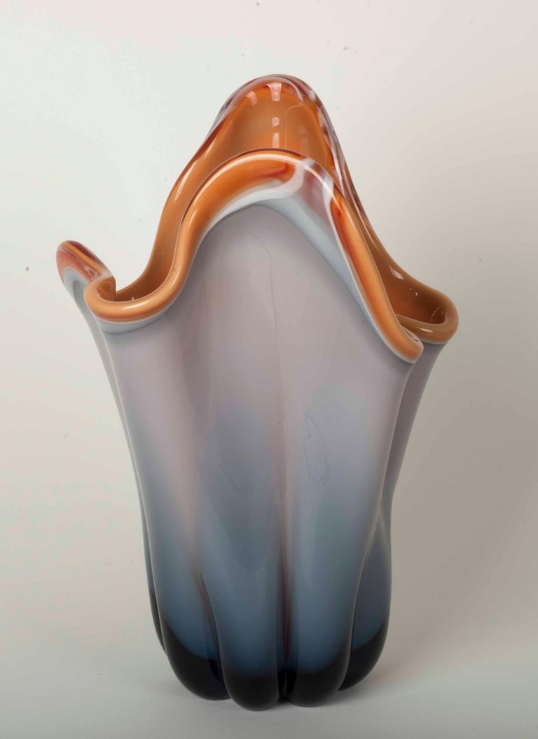 Modernist flower vase with orange interior and gradient of grays in exterior.