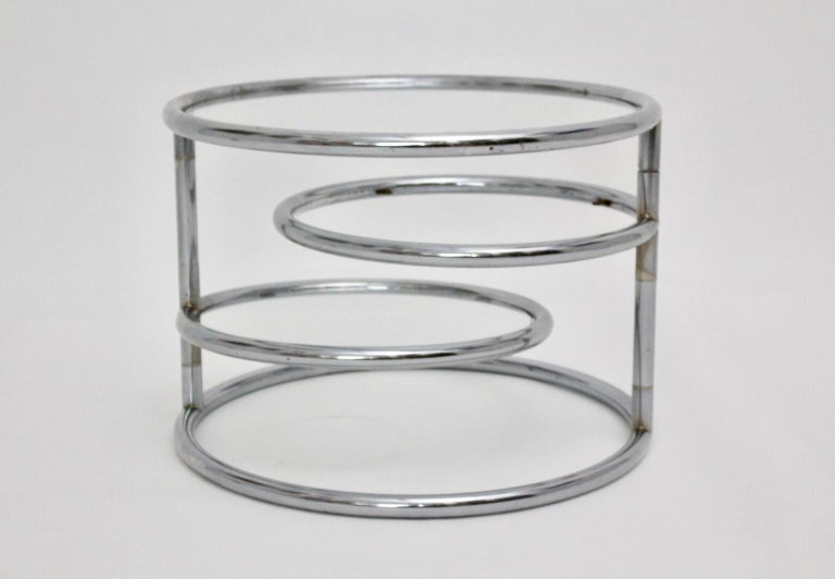 This presented coffee table from circa 1970 shows a chromed metal tube steel frame with a clear glass top and two revolving clear glass plates. Very good vintage condition with signs of age and use. The glass plate shows fine
