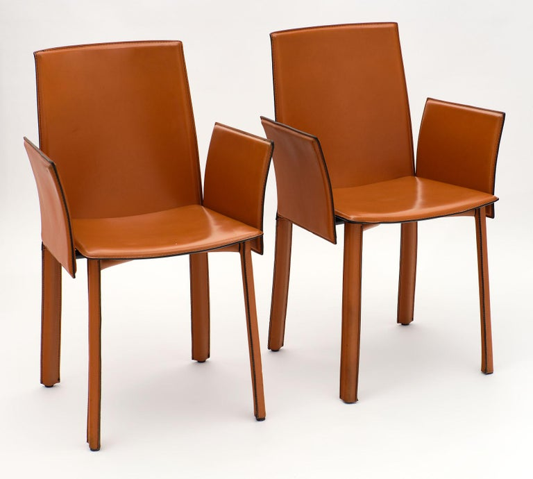 Vintage modernist orange leather armchairs from Italy. This pair is in excellent vintage condition and fully covered in the beautiful, warm leather. We love the lines, reminiscent of Carlo di Carli.