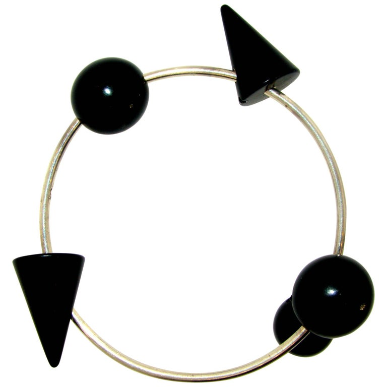 Geometric in design with blackened steel elements (element's directions can be changed), set along a narrow tube of polished steel to create quite an unusual design. It expands slightly for ease of putting on. In excellent condition, Three inches in